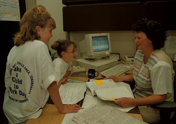 98/04/23--KIDS AT WORK--DAN CAPPELLAZZO PHOTO--DEBBIE TJADEN, OF UNIFAX CORP. NF, WORKS WITH HER TWO DAUGHTERS, ELISE, 9 STANDING, AND ASHLEY 12 IN THE WHIRLPOOL STREET OFFICE.<br /> <br /> 1A