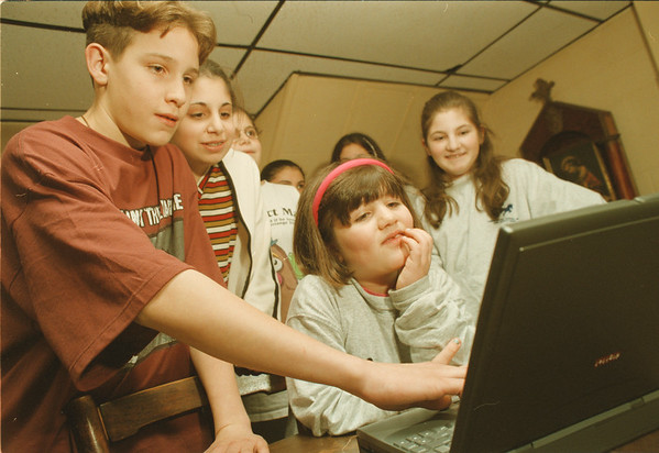 98/01/05--Armenian church--Takaaki Iwabu photo-- Sam Peller, left, 13, reaches to a lap-top computer as he and other members of St. Sarkis Armenian Church's Sunday School send an e-mail message to Anna Pkhrikian, an Armenian woman with leukemia staying at Ronald McDonald House in Buffalo.  Others in front, from left, Lisa Ohanessian, Maral Otabachian and Silvia Otabachian.   --local, bw, Tuesday