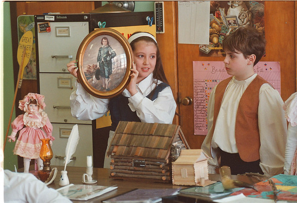"3/18/97 Colonial Day - James Neiss Photo - Toni Alfiere 9yrs/4th grade shows how children were dressed in differant social classes durring colonial times as classmate daniel Fasciano 9/4th looks on before showing what log cabins looked like durring ""Colonial Day""  at the Mount Carmel School."
