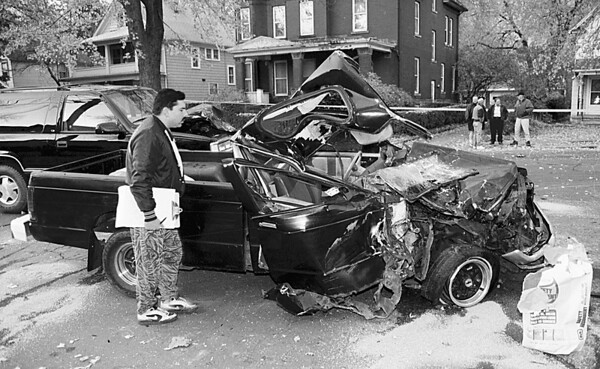 98/11/02 MVA - 3 Cars--Vino Wong Photo--<br /> Officer Leslie Kachurek peers into the damage pick-up truck during a three vehicle injury accident along the intersection of Niagara Avenue and Lockport Street Monday.