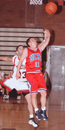 98/12/08 nw/nc hoops--dan cappellazzo photo--ncÕs anthony arist (red) drives for the layup against nwÕs nicholas condino in first half action.