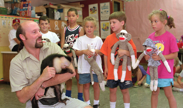 """98/07/29 Monkey Business *Dennis Stierer Photo -<br /> Carmen Prestio, a handler with Monkey Business, the  primate rehabilitation center in Niagara Falls brought some monkey's down to Roy B. Kelly school to see some kids. He's holding """"Saro"""", a Cebus Capuchin monkey as the children look on. They are: from the left:  Jonathon Greig, Dennis Weaver, Miller Barmasse, Andrew Granchelli, and Sadie Weaver."""
