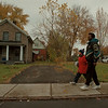 11/5/97-- Grove Avenue--Takaaki Iwabu photo-- Neighbors walk by the house on 930 Grove Ave, where the City's latest homecide was took place. <br /> <br /> Friday, color, 1A