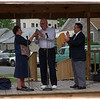 "97/09/13 Gluck Park Rededication 2 - James Neiss Photo - Sr. Mary Francis Bassick presents Bob Gedeon, coordinator of the Gluck Park Restoration project, with a replica of a large boulder in the center of Gluck Park,  as thanks for all his effort. They affectionately were calling the boulder ""Gedeon's Rock"".  Master of Ceremonies Vince Spadorcia, President of the Middle City Neighborhood Assoc. applauds at right."
