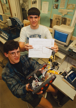 "5/1/97 Newfane Robotics - James Neiss Photo - L-R - Chad Taylor 18/12 and Bill Scott 17/12 won 1st place in the ""Self Controlled Journey Robot"" with their "" Jerky Bot - 101"" robot, at the Society of Manufacturing and Engineers Robotic Competition at Ohio Northern University. The robot is controlled by light sensitivity and would go forward following white and turn when it encounters Black. Bill Scott is holding the course outling."