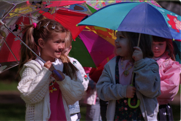 """98/04/22 Umbrella parade2-Rachel Naber Photo-Chelsie Goodrich (left) and Elizabeth Coulson go on a spring walk with classmates from the First Baptist Nursery School to learn about signs of spring and have fun with learning the letter """"U"""" for umbrella."""