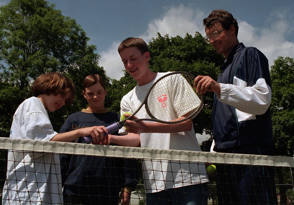 98/06/04 Summer Tennis *Dennis Stierer Photo - Katie Taylor,11 and Kevin Crawford,14 get a helping hand on their grip from Tim Lyster, one of this summers' tennis assistant instructor's as head instructor Dave Shamback looks on.<br /> SEE ADDITIONAL INFO ON ATTACHED SHEET.