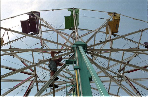 98/08/04 County Fair 2 - James Neiss Photo - Preston Cole of Delaware, a ride operator with Amusements of Buffalo, tightens ferris wheel cables in preperation for the openig of the Niagara County Fair..