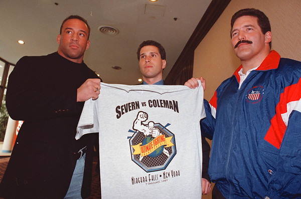 2/6/97--ultimate fighting--DAN CAPPELLAZZO PHOTO--(LTOR)ULTIMATE FIGHTERS MARK COLEMAN AND DAN SEVERN FLANK SEG SPORTS C.O.O. DAVID ISSAACS HOLDING UP A SHIRT OF THE NIAGARA FALLS FIGHT THAT DID NOT TAKE PLACE DUE TO A STATE RULING.<br /> <br /> 1A
