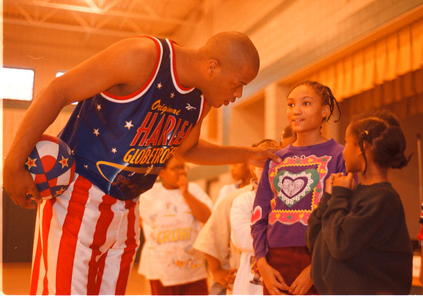 "2/19/97-- globetrotters-- Takaaki Iwabu photo-- James ""Jumbo"" Bacon, center for Harlem Glovetrotters, talks to a 9-year-old  Marina Carter of Niagara Falls duirng the clinic he gave at Fammioy Resource Cetner Wednesday.\\ local, bw"