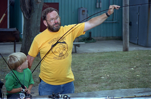 98/08/06 Scout Anglers-Rachel naber Photo-Eric Mitchell from Den #3 watches pack leader Kevin Johnson demonstrate the differences between fishing poles used for the sport.
