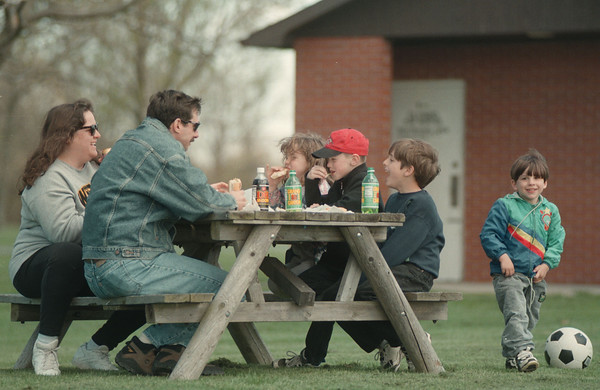 98/04/25--State Park --Takaaki Iwabu photo-- Jacob Britten, right, kicks a soccer ball while his family members and a friend eat lunch nearby at Beaver Island State Park on Grand Island Saturday. (for Glynn's story on State Parks) <br /> <br /> Monday Topic, color
