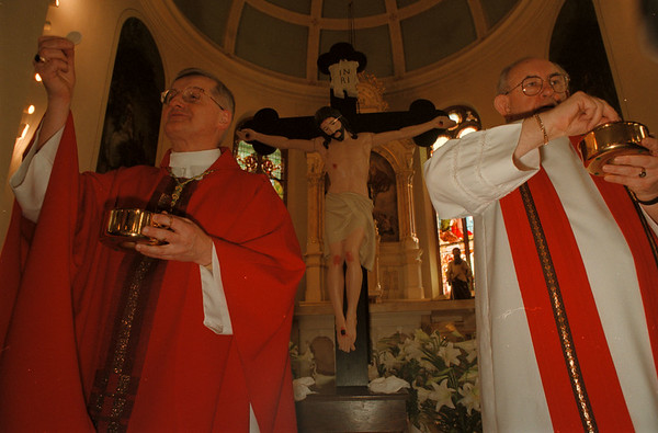 98/04/10-- good friday --Takaaki Iwabu Photo -- Bishop Edward M. Grosz, left, and Msgr. Edward J. Scanlan exercise a communion in front of statue of Jesus during the Good Friday mass at Holy Trinity Church at 14th and Falls St. in Niagara Falls.      -- 1a, color, Saturday
