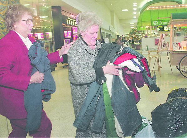1/18/97-- coat donation-- Takaaki Iwabu photo-- Gloria McMurray, right,  Niagara Falls, drops off clothes donating to Niagara Community Action Program Saturday at Summit Park Mall. Behind her is Mildred Harvey, Neighborhood Center's coordinator. Donated clothes will be given away February 5th at the Program office in 564 19th St.