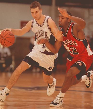 98/01/31--NU Basket--Takaaki Iwabu photo-- Purple Eagles  Luke Dobrich, left, goes around Fairfield University's Charles Farrow during Saturday's game at Niagara University. <br /> <br /> color, Sunday