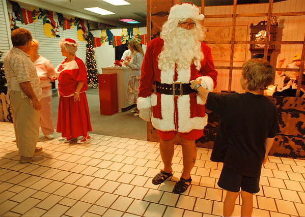 7/3/97 festival of light 2--Takaaki Iwabu photo-- A summer Santa (with shorts) greets a Jesse Long, 8, after the ribbon cutting ceremony for kicking off this year's Festival of Lights at Rainbow Center Friday. <br /> <br /> local, secondary or Grapevine