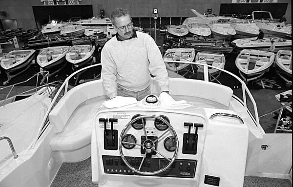 1/8/97--BOAT SHOW--CAPPY PHOTO--BOB COPELIN, CO-OWNER OF COLLINS MARINA, TONAWANDA, BUFFS UP A 35FT CABIN CRUISER, RETAIL VALUE $160,000, AT THE NFCC.