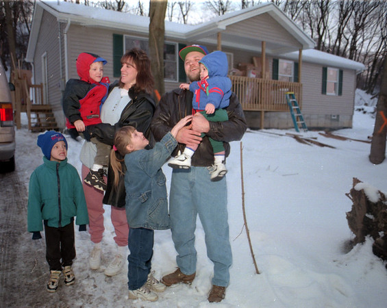 98/01/20--HABITAT FOR HUMANITY--DAN CAPPELLAZZO PHOTO--THE BURBEE FAMILY,( LTOR)5-YR-OLD TIMOTHY, 4-YR-OLD GARY HELD BY MOM ANGELA, 6-YR-OLD ANGELIKA, FRONT CENTER, AND FATHER ED HOLDS 10 MONTH OLD CHRISTOPHER STAND IN FRONT OF THEIR NEW SCOVELL ST. HOME AS PART OF HABITAT FOR HUMANITY.<br /> <br /> LKP