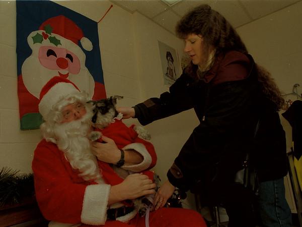 "97/12/15-- SPCA/Xmas 2--Takaaki Iwabu photo-- Sherrie Schroeder, Town of Wheatfield, passes her Miniture Schnauzer ""Gretchen"" to Santa Clause for picture taken at SPCA's Christmas party Sautrday."