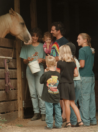 98/09/03--9/14HORSES5--DAN CAPPELLAZZO PHOTO--THE LYON FAMILY; CHERI FEEDING HORSE, AND TODD HOLDING 1.5 YR OLD DAUGHTER JOCIE ARE SURROUNDED BY CHILDREN WHO CALL THE FARM A SECOND HOME.<br /> <br /> SUNDAY FEATURE