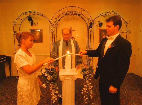 98/02/13 Wedding Chapel 2 - James Neiss Photo - Rob Johnson of Columbus, Indiana and his new bride Christa Johnson signify the becoming of one with the lighting of a single candle.  The Rev. Dr. Ken Smith looks on,  during cerimonies at the Niagara Wedding Chapel.
