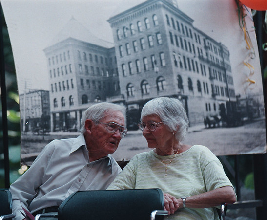 7/28/97--OLD FALLS STREET--DAN CAPPELLAZZO PHOTO--98-YR-OLD WRAY HILTS REMINISCES ABOUT OLD FALLS STREET WITH HIS WIFE MARGE, 87 WHILE SITTING IN FRONT OF AN OLD PHOTO OF THE GLUCK BLDG, BUILT AT THE TURN OF THE CENTURY AND BURNED DOWN JAN 29TH 1959.  MR HILT WORKED AT MILLER AND STRONG PHARMACY, 1ST AND FALLS ST., FROM 1914 TO 1918 WHILE IN HIGH SCHOOL. THE HILTS LIVE IN LASALLE.<br /> <br /> 1A