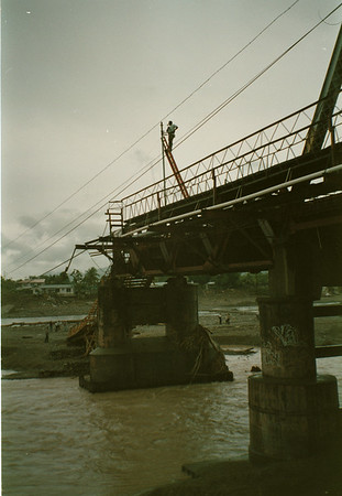 98/25/98 Honduras Relief 3 - Valerie E. Pillo - A repairman works on electrical wires on what's left of the Saopin Bridge which was washed away by flood waters due to hurricane Mitch.