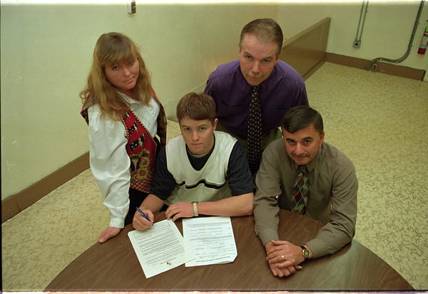 98/11/11  Johnson Family - Vino Wong Photo - (front left) Kyle Jonson prepares to sign a letter of intent, sitted next to his coach Gary Nannella and his parents Janyce and Al Johnson.