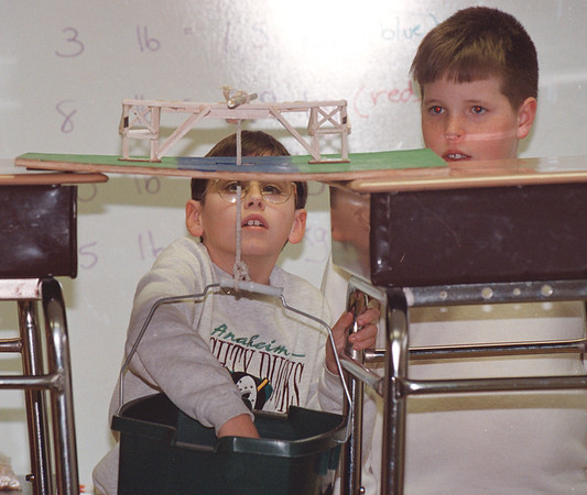 3/20/97--ERRICK RD SCHOOL/BRIDGE--DAN CAPPELLAZZO PHOTO--10-YR-OLD RICHIE SABIN PLACES A WEIGHT INTO A BUCKET, TESTING THE STRENGTH OF A BASLA WOOD BRIDGE BUILD WITH THE HELP OF FELLOW STUDENTS ERIC KATZ (LOOKING ON) AND ERIC THUMAN (NOT PICTURED) IN MR LIVINGSTON'S ERRICK RD SCHOOL 5HT GRADE MATH/PHYSICS CLASS