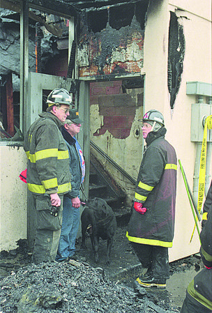 """1/2/97 Wacky World Fire - James Neiss Photo - Miles Gebauer, Capt. of Fire Investigations, Bruce Ludemann Special Deputy, Niagara County sheriffs Dpt with his dog """"Paul"""" and Richard Frommert, Fire Investigator try to determan how the fire began."""
