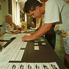 98/09/15 Primary Vote - James Neiss Photo - Chris Qualina of Beattie Ave. , foreground, and brother Anthony Qualiana, back with hat, both filled out ballots for todays primary. They were new residents and had to do it by hand. Back, L-R are Elections inspectors Amilia Scirati and Lisa Windnagle and were watching over things at the Board of Education Building.