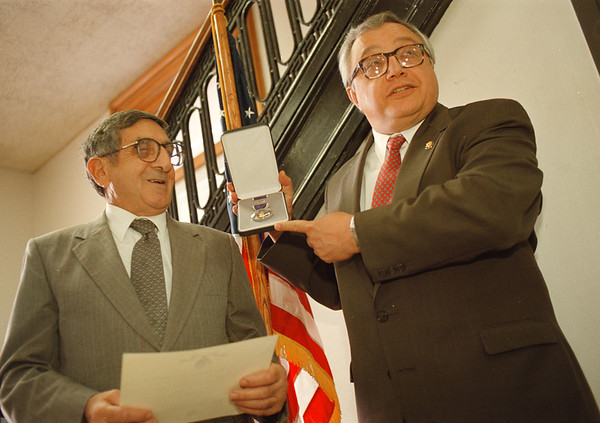 97/10/15-- purple heart --Takaaki Iwabu photo-- Anthony Moley, 75, left, receives the Purple Heart from Congressman John LaFalce at Niagara Falls post office Wednesday. Moley waited for the award for 52 years. <br /> <br /> local, bw, Thursday
