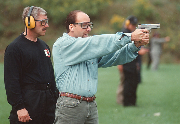 9/11/97-- Firearms --Takaaki Iwabu photo-- Brandy Scrufari fires a gun with a help of FBI special agent Tom Doktor during the Outdoor Firearms Shoot by Buffalo Office of FBI Thursday at Tonawanda Sportsmen's Club. <br /> <br /> 1A, Friday, color