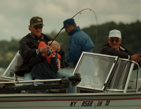 98/09/08 Fishing Derby - James Neiss Photo - The Buffalo Bills Chris Mohr helps his son Garrett Mohr, 5yrs, reel in a big one during the 3rd Annual Riedman Insurance Fishing Classic, to Bennifit Big Brothers Big Sisters of Niagara County,  on the Niagara River in Lewiston. At right in white hat, Fred Elenfeldt of NT, a fishing guide, volunteered his services for the event.
