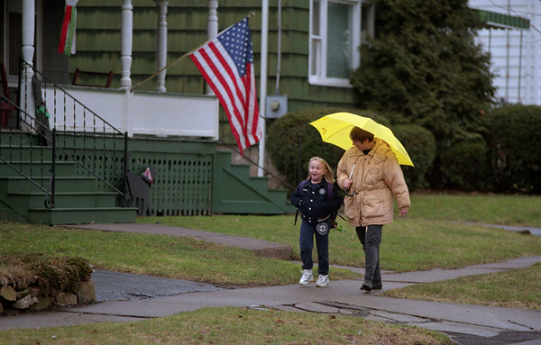 98/03/03  Walking in the Rain *Dennis Stierer photo - After getting off at the bus stop,  7 year old Carissa Wertman has a nice walk home with mom, Bonnie on Webb Street.