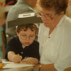 "98/25/98 Thanksgiving Crafts - James Neiss Photo - Christopher Seel, 5yrs/KG and his Grandmother Terry Jones of NF, both work on Pilgram & Native American Head Dresses for Thanksgiving. They then enjoyed ""Thankfull Soup"" and Corn Bread made my the students at the Prince of Peace School."