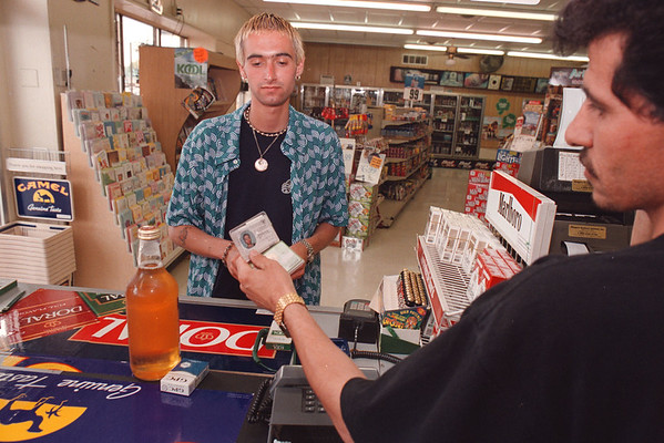 7/1/97--SMOKING LAWS--DAN CAPPELLAZZO PHOTO--JAY JANOSSY, 22 OF TORONTO SHOWS HIS PROOF OF AGE TO SALAM ALHAJJAJI AT THE GAS PLUS ON THE CORNER OF NFB AND MILITARY RD.<br /> <br /> 1A NEWS MONDAY