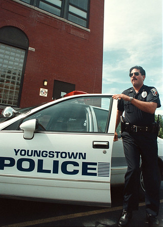 97/08/16-- Youngstown Police--Takaaki Iwabu photo-- Youngstown Police officer David Jaworek gets off the patrol car as he was on duty Saturday in front of Red Brick Building in Youngstown.  (for Lisa's story on burglary in the area..) <br /> <br /> tmc