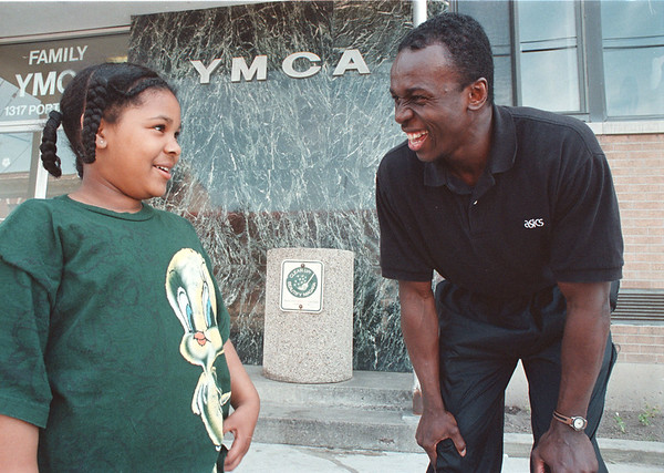 5/24/97-- golfers 2--Takaaki Iwabu photo-- Dexter Harris of (Niagara Falls) YMCA Youth Division talks to Michele Hamilton, 5, ;left.  --- Harris is quoted on Bills story on Tiger Woods and kids golfers.  Secondary photo, if you need it. <br /> <br /> sports, Sunday, color