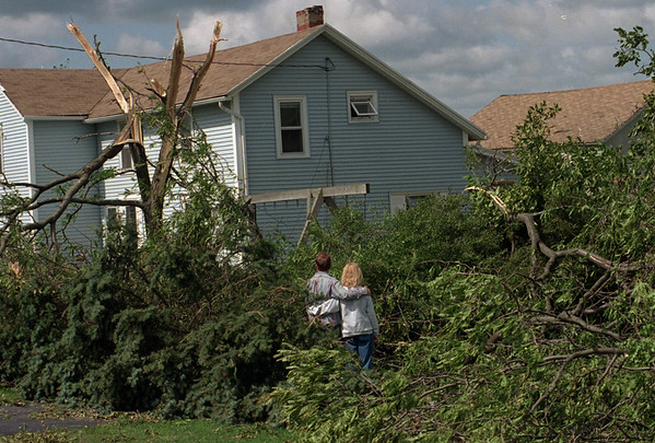 """98/09/08--STORM DAMAGE--DAN CAPPELLAZZO PHOTO--PETER AND MEGAN GAMIN STAND IN THE CENTER OF DOWNED TREES, WHAT WAS THE ENTRANCE TO THEIR DRIVEWAY, AT 7987 GASPORT RD. NEARLY ALL THE TREE ON THEIR PROPERTY WERE TOPPED BY THE STROM. """"PETER GAMIN SAID HIS SON AND GIRLFRIEND JUST ESCAPED INJURY AS THE STORM BLEW IN WITH LITTLE WARNING.<br /> <br /> LKP"""
