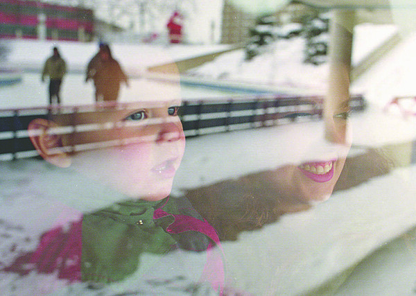 1/11/96-- end of lights--Takaaki Iwabu photo-- Images of skaters are reflected on the waiting room's window at Marine Midland Centennial Ice Rink as Sonia Czechorowski and her 1.5 year old son Christopher follow their companions action Saturday. (The pic for Festival of Light wrap-up story)<br /> <br /> 1A Tuesday, Color