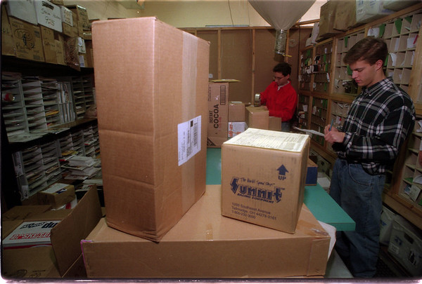 97/12/12 Holliday Package Traffic - James Neiss PHoto - CBI, Consolidated Business Internationl at 1402 Pine Ave was doing a brisk business handling holliday packages. L-R , Bob Galvano and Les Bridgeman, both Shipping clerks, go over some of the days shipments.
