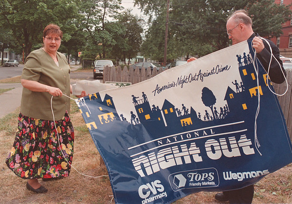 8/1/97 night out--Takaaki Iwabu photo-- Geri Mondi, office administrator for Senator Anthony Nanula, and Monsignor William Stillwell of St. Mary of The Cataract Church, try out the National Night Out banner on the fence at Ferry Ave. and 6th St., where many locals will gather for the ralley Tuesday.
