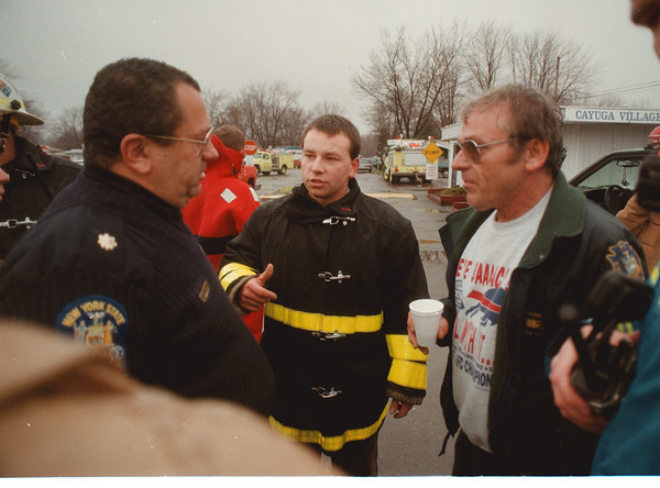 97/01/08 Flooding - James Neiss Photo - L-R - Dave Krieman, Associate Program Director with the NYS Dpt. of Health,  Greg Slusser Niagara #1 Assistant Chief, vms and Dave Slusser Niagara #1 Chief, discuss a possible plan of action in the evacuation of residents of Cayuga Court.