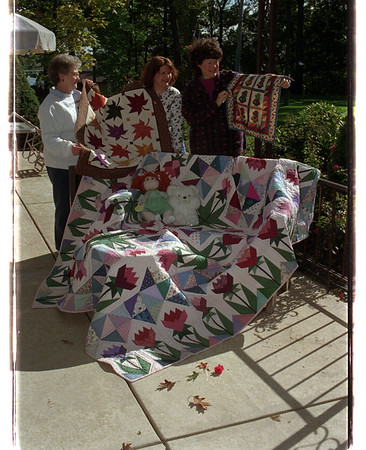 97/10/01 Quilters 2 - James Neiss Photo - L-R - Janet Bianca, Judi Drozdowski and Joan Staub. Grand Island, show off the Raffel Quilt called Tulip Garden which is spread out ont he bench.  and others that they made.