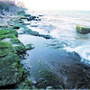 98/12/04 Lake Ontario Low *Dennis Stierer Photo <br /> With the water so low on Lake Ontario, many of these rocks and coastline are now exposed.  Normally these rocks would be totally covered by water.  The effect can be seen by the amount of green moss growth on the rocks.