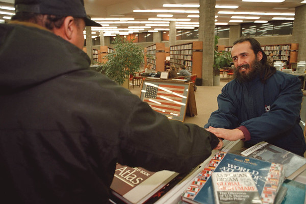 2/11/97--KINDNESS WEEK/HOMELESS GUY--DAN CAPPELLAZZO PHOTO--GARY RIZZO, A HOMLESS N.F. SHAKES THE HAND OF NOEL GONZALES, A LOCAL MAIL CARRIER, AT THE NF LIBRARY WHERE RIZZO SPENDS MOST OF HIS TIME. GONZALES HELP HOUSE RIZZO AT THE YMCA RECENTLY.<br /> <br /> 1A