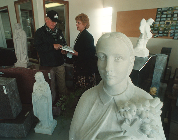 5/15/97 Niagara Monument 4 - James Neiss Photo - Elaine Farchione-Rosselli, Co-owner of Niagara Monument Works Inc., shows customer Floyd Clark, Past President of the Wilson Lions club, who was getting material for repairing grave markers which the Wilson Lions club members have been doing at Wilson Area Cemetaries for the past 10 years. The two are surrounded by imported hand carved statues.
