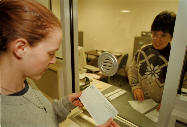 98/11/04 Ticket Amnesty - James Neiss Photo - Amie Cumpson, 19yrs of Falls Street looks over the recipt, received from Account Clerk Michele Etopio, for paying her back tickets. An amnesty program is going into effect for people who have not paid their tickets.
