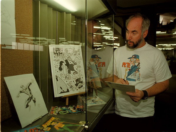 98/09/14 Comic Collector - James Neiss Photo - Phil Conley, a comic Delaler, shows off his family collection of original comic artwork dating from the 1940Õs on, at the Niagara Falls Main Library. The art work will be up until the end of September. 282-1236 is his home number.